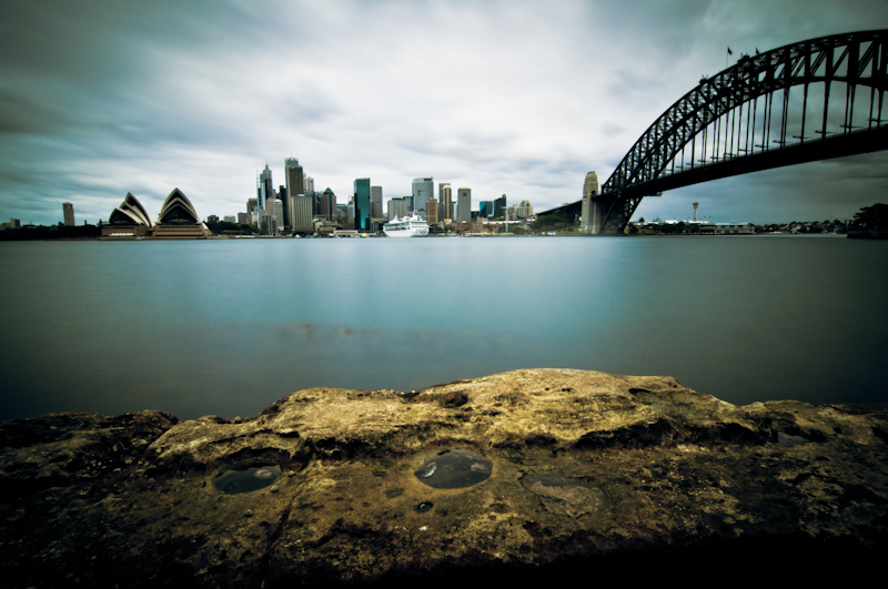 A long exposure photo from Sydney, Australia. The Rocks, Sydney Opera House, central city and Harbour Bridge. Sydney harbour and a ship.