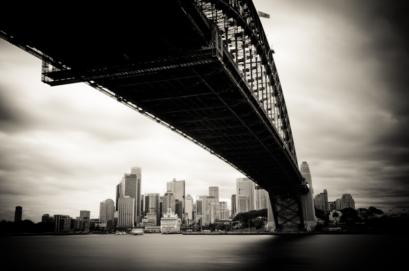 Blank and white photography from Sydney, Australia. Cityscape of Sydney Harbour Bridge and skyscraper buildings. Long exposure photography by photographer Kimmo Savolainen.