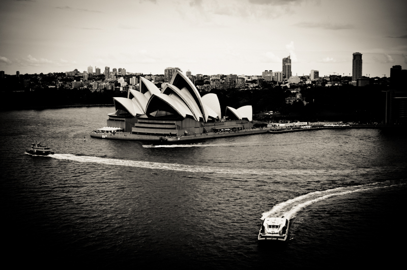 Black and white picture of Sydney Opera House and ferries in the water. Sydney cityscape in black and white from Australia.