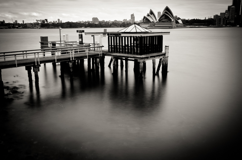 A long exposure black&white photo of a ferry pier in Sydney. Opera House , water and the city.